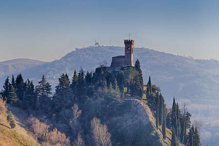 crenellated tower: A  medieval crenellated clock tower stands on a peak overlooking the valley of a country of farmland, bushes, cypresses and other tress in the mist of a sunny winter day