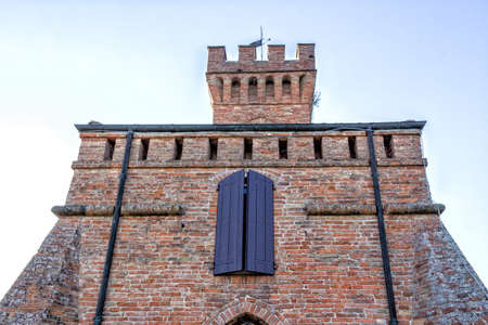 crenellated tower: A  medieval crenellated brick wall clock tower in a sunny winter day Stock Photo