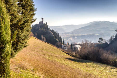 crenellated tower: A  medieval crenellated clock tower stands on a peak overlooking the valley of a village and a country of farmland, bushes, cypresses and other tress in the mist of a sunny winter day Stock Photo