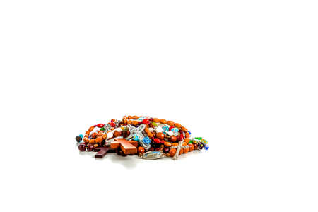 messily: Some Rosary beads piled messily. They are different for colors, shapes and materials: brown and red wood, green, red, blue or glass stones, long or short size