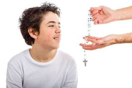 long sleeved: A happy Hispanic boy wearing a white long sleeved t-shirt smiles receiving Rosary glass beads given by bare adult hands Stock Photo
