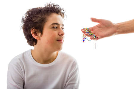 dishevelled: A happy Hispanic boy wearing a white long sleeved t-shirt smiles receiving Rosary glass beads given by bare adult hands Stock Photo