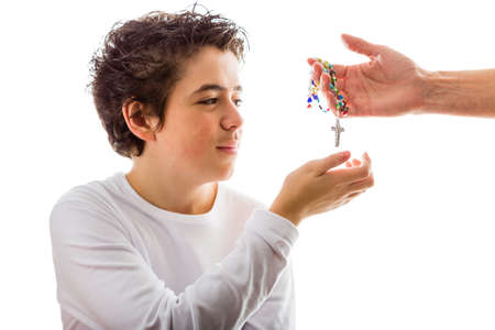 long sleeved: A happy Hispanic boy wearing a white long sleeved t-shirt smiles receiving with his right hand a Rosary made with glass beads given by bare adult hand