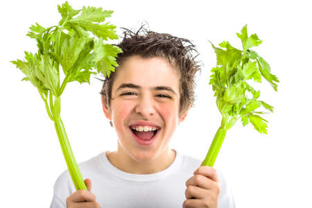 long sleeved: Handsome hispanic boy with soft skin  in white long sleeved t-shirt is smiling while holding green celery sticks with both hands Stock Photo