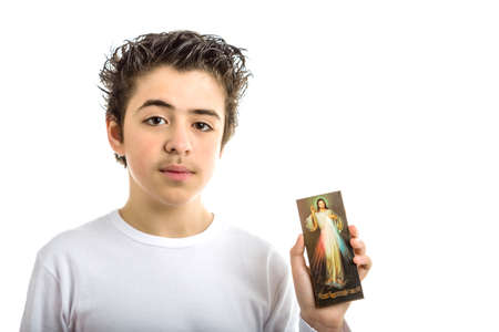 merciful: A hispanic boy holds a picture of Merciful Jesus