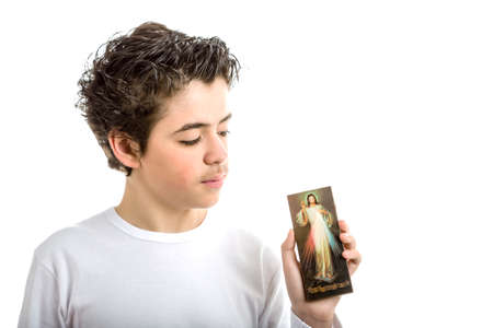 hispanic boy: A hispanic boy looks at a wooden picture of Merciful Jesus hes holding with left hand Stock Photo