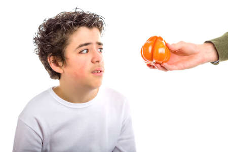 disgusted: A Hispanic boy takes a disgusted look to an orange tomato that an adult hand offers him coming from the right