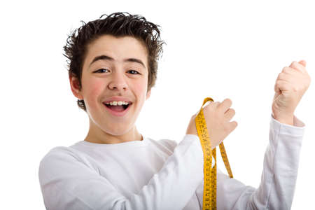 sleeved: Happy hispanic boy in white long sleeved t-shirt smiles while measuring the muscle of his left arms with yellow meter tape