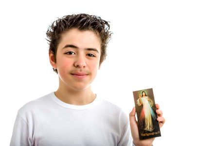 hispanic boy: A happy hispanic boy smiles holding a wooden picture of Merciful Jesus with left hand