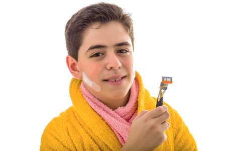 smooth skin: A Hispanic boy with smooth skin wears a yellow bathrobe and a pink towel: he has patches on his face but he smiles holding the razor after shaving Stock Photo