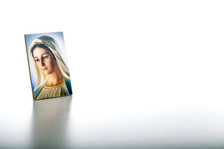 Icon of Our Lady of Medjugorje the Blessed Virgin Mary isolated on white background with matte reflection on white table. Stockfoto