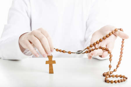 sleeved: A Latin boy holds Rosary beads with both hands. He wears long sleeved shirt Stock Photo