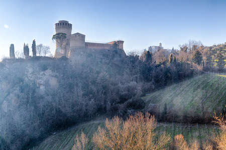 bulwark: The brick walls of a medieval fortress and a sanctuary with belfry devoted to Blessed Virgin on cultivated hills in a misty countryside