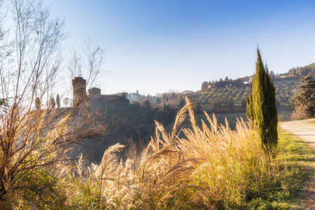 bulwark: The brick walls of a medieval fortress and a sanctuary with steeple devoted to Blessed Virgin Mary on misty hills in a countryside of bushes and cypress trees from bulwark in a winter sunny day Editorial