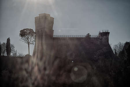unearthly: The brick walls of a medieval fortress under spooky sunlight in a misty countryside
