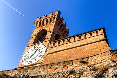 crenellated: A  medieval crenellated brick wall clock tower in a sunny winter day Stock Photo