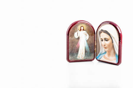 the merciful: Icons in a wooden rounded case of Merciful Jesus and Our Lady of Medjugorje, the Blessed Virgin Mary isolated on white background with matte reflection on white table. Stock Photo