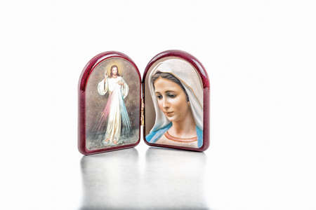 merciful: Icons in a wooden rounded case of Merciful Jesus and Our Lady of Medjugorje, the Blessed Virgin Mary isolated on white background with matte reflection on white table. Stock Photo