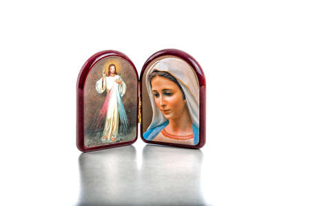 Icons in a wooden rounded case of Merciful Jesus and Our Lady of Medjugorje, the Blessed Virgin Mary isolated on white background with matte reflection on white table. Stock Photo