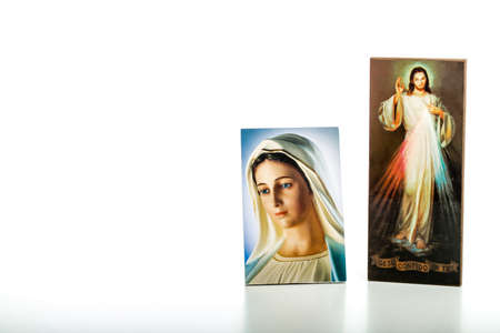 spiritual woman: Icons  of Merciful Jesus and Our Lady of Medjugorje, the Blessed Virgin Mary isolated on white background with matte reflection on white table. Stock Photo