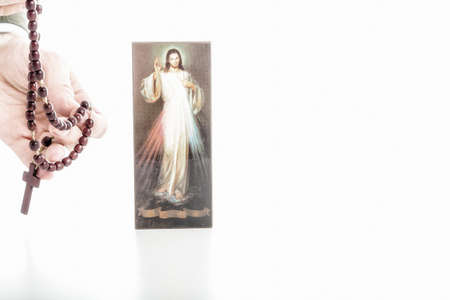 merciful: Hand offering brown Rosary beads and a picture of the Merciful Jesus with blank ribbon