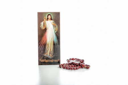 merciful: Isolated on white background, rosary beads and  an icon with the picture of the Merciful Jesus without writings on the ribbon where you can write your language version of Jesus, I trust in you