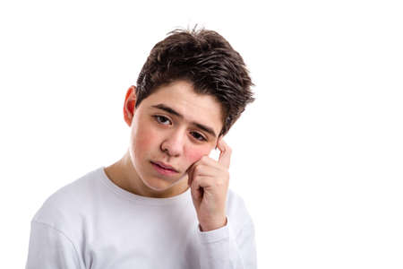cogitate: Worried Hispanic boy with acne skin in a white long sleeve t-shirt ponders holding his head with index finger of left hand