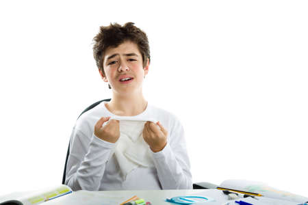 hankerchief: Cute Latin boy sadly sitting in front of homework wearing a white long sleeve t-shirt and holding hankerchief to wipe tears