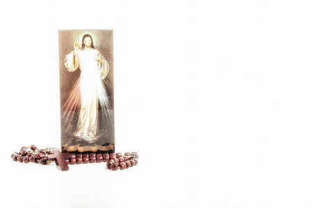 christian trust: Brown Rosary beads and a picture of the Merciful Jesus: the translation of the Italian writing on bottom is Jesus, I trust in you Stock Photo
