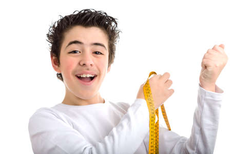 long sleeved: Smiling Caucasian boy with soft and smooth skin in white long sleeved t-shirt measuring the muscle of his left arm with a yellow tape measure
