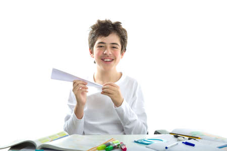 shaping: A Latin boy  with soft and smooth skin is playing with paper airplane sitting in front of homework. He is holding it with the right hand while the left hand is shaping the tip