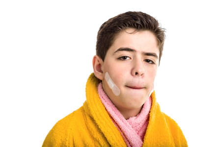 reddening: A Soft skinned Latin boy wears a yellow bathrobe with a pink towel: he has some patches on his face after shaving but he looks calm and confident while stretching the skin above the lip to check cuts