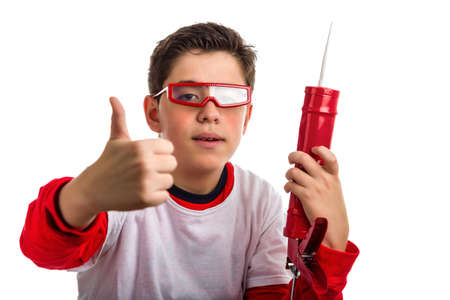 caulk: A Soft skinned Latin boy wearing red goggles holds a red caulk gun with right hand smiling while he makes success sign with right hand Stock Photo