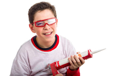 caulking: A Soft skinned Hispanic boy wears red goggles with clear lenses and with right hand smiling  he holds a red caulking gun