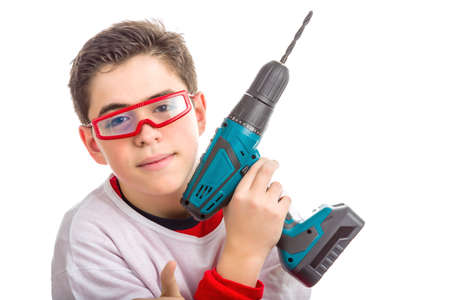 red skinned: A Soft skinned Hispanic child wears red goggles with clear lenses and with right hand he holds a green cordless drill: he looks calm and confident