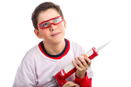 caulk: A Hispanic boy with soft skin with red protective goggles dreams smiling while holding a red caulking gun Stock Photo