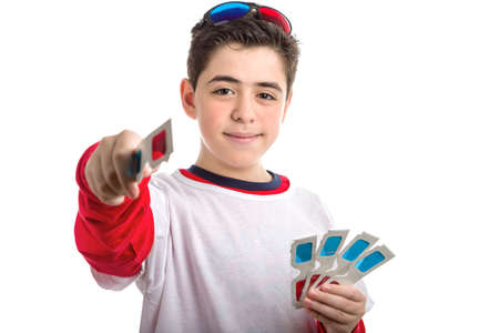 soft skin: A Caucasian boy with soft skin wears a pair of black 3D Cinema plastic goggles on his head with red and blue lenses and holds 4 white paper eyeglasses with left hand  while offering one with right hand