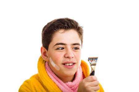 squint: A Hispanic boy wears a yellow bathrobe with a pink towel around his neck: he has some patches on his face and smiling stares with crossed eyes at the razor he used for shaving Stock Photo