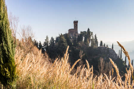 crenellated: A  medieval crenellated clock tower stands on a peak overlooking the valley of a country of farmland, yellow bushes, cypresses and other tress in the mist of a sunny winter day