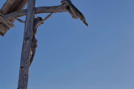 weathering: Backlight of wood-carved statue of crucifixion of Jesus Christ. Wood shows signs of weathering