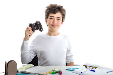 short sleeve: Happy Caucasian smooth-skinned boy in short sleeve t-shirt plays with a game controller sitting in front of his  homework on desk