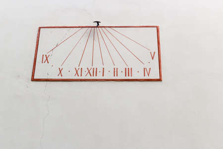 horologe: Simple grunge red sundial on pastel wall Stock Photo