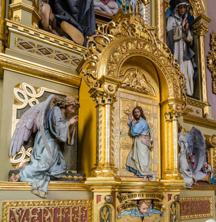 jesus standing: Wood carved statue of Jesus Christ between two angels  standing at a golden door and knocking as in sentence from Apocalypse book from the Parish Church of Urtijëi in Italy Stock Photo