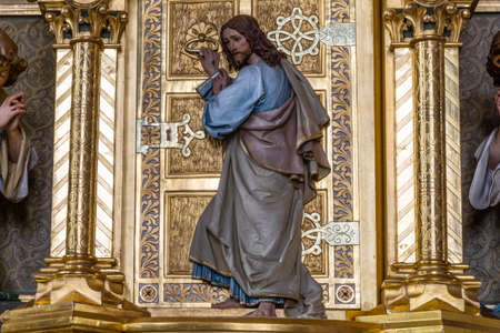 Wood carved statue of Jesus Christ standing at a golden door and knocking as in sentence from Apocalypse book Stock Photo