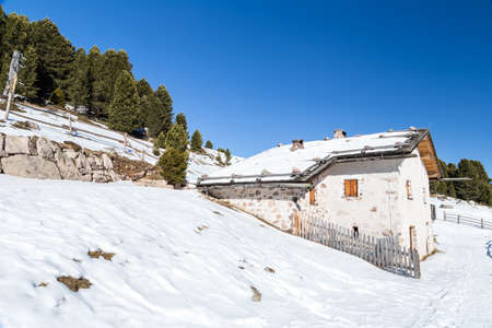 Alpine chalet surrounded by a fence in the snow among snowy peaks and pine forest on a bright sunny day in winter photo