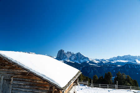 Alpine chalet surrounded by a fence in the snow in front of a panorama of snowy peaks on a bright sunny day in winter on Dolomites Alps