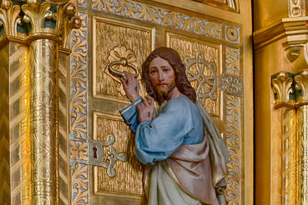 jesus standing: Wood carved statue of Jesus Christ standing at a golden door and knocking as in sentence from Apocalypse book Stock Photo