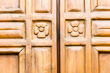 marquetry: marquetry wood of the door entry of the Facade of the VII Century Saint Peter in Sylvis parish church in Italy Stock Photo