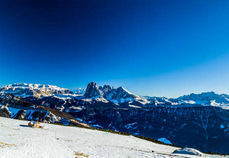 chalet: panorama of the Dolomites with chalet, snow-capped peaks and conifers Stock Photo