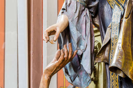 pauper: Right hand of wood carved statue of rich woman giving coin to left hand of beggar as charity gesture Stock Photo